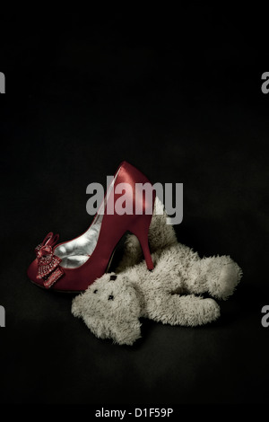red shoe steps on a teddy bear - Stock Photo