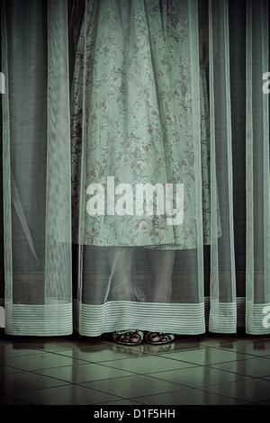 a girl is hiding behind a curtain - Stock Photo