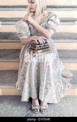 a woman in a floral dress is holding a pile of antique books on her lap - Stock Photo