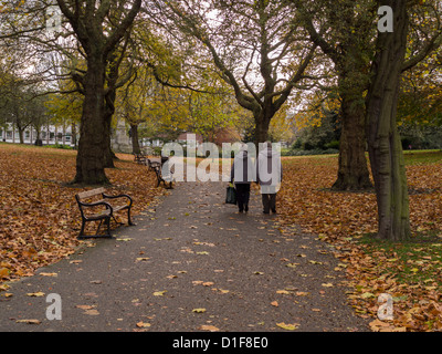 Man and Woman holding hands walking along a  leafy footpath in parkland with trees and fallen leaves Sheffield UK - Stock Photo