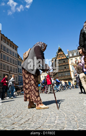 Old Woman begging on the Cathedral Square in Strasbourg, France - Stock Photo