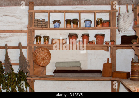 antique clay storage jars on wooden shelving - Stock Photo