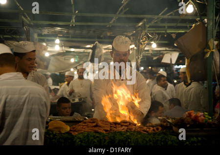 A chef grilling meat at food stalls in the main square, Jemaa el Fna, in Marrakech, Morocco, North Africa - Stock Photo