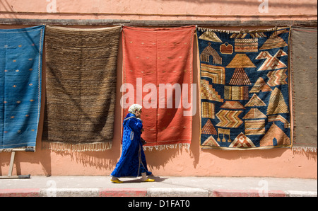 A woman in Islamic dress walking by a wall hung with carpets in the Medina in Marrakech, Morocco, North Africa, - Stock Photo