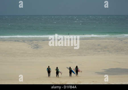 Four surfers in wet suits carrying boards and heading down the beach in St. Ives, Cornwall, England - Stock Photo