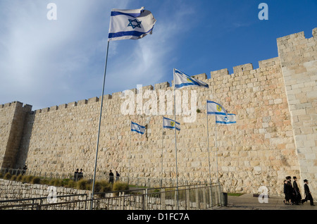 View of City Walls with Orthodox Jews and Israeli flag. Old City, Jerusalem, Israel, Middle East - Stock Photo