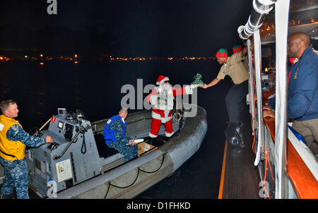 Santa Claus delivers cookies to the crew of the admiral's barge during the 2012 Holiday Ship & Submarine Lighting - Stock Photo