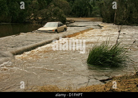 Car been driven through dangerously deep and fast flowing floodwaters of rivercrossing a road in Australia - Stock Photo
