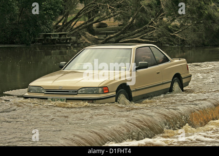 Motorist in Car driving through deep and dangerously fast flowing flood waters where river crosses a road in Australia - Stock Photo