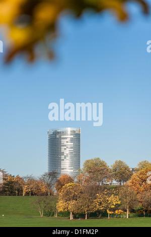 Posttower, the headquarter of Deutsche Post DHL in Bonn, seen from the leisure park Rheinaue, framed by autumnal leafs