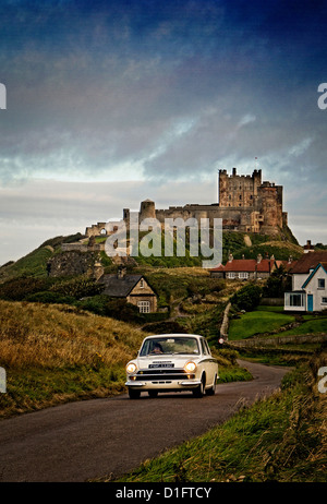1965 Ford Lotus Cortina driving on the Northumberland coastal route with Bamburgh castle in the background. - Stock Photo