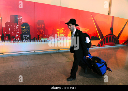 Young Jewish American man arriving from Israel to John F. Kennedy International Airport in New York USA - Stock Photo