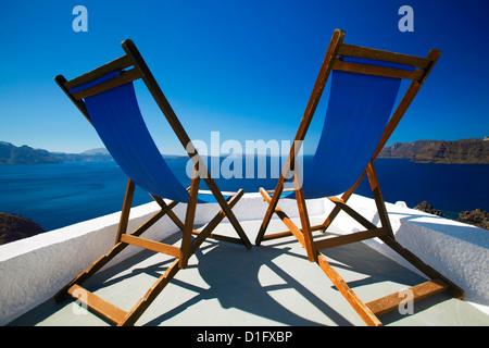 Deck chairs on terrace overlooking ocean, Santorini, Cyclades, Greek Islands, Greece, Europe - Stock Photo