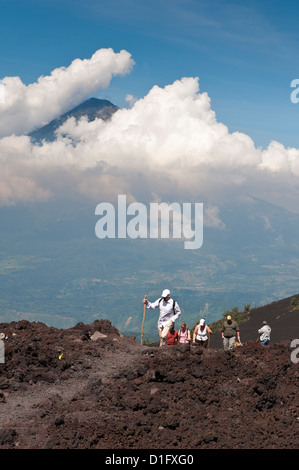 Climbing Pacaya volcano, with Fuego Volcano in distance, Antigua, Guatemala, Central America - Stock Photo