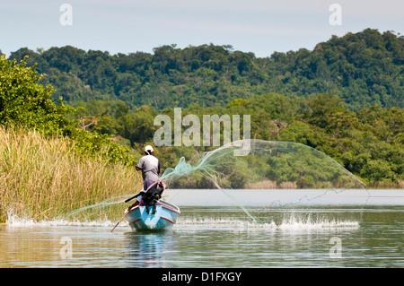 Fisherman casting net on Lake Izabal (Lago de Izabal), Guatemala, Central America - Stock Photo