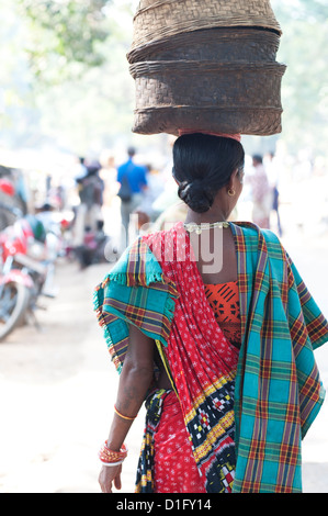 Woman at weekly tribal market wearing brightly coloured clothing and carrying baskets on her head, Bissam Cuttack, - Stock Photo