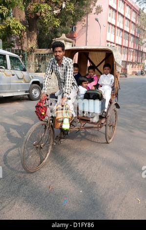 Cycle rickshaw taking children to school, Chandernagar, West Bengal, India, Asia - Stock Photo