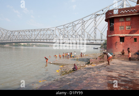 Men performing ablutions on ghats beneath the Howrah Bridge in the early morning, Kolkata (Calcutta), West Bengal, - Stock Photo