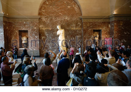 tourists taking photographs of the Venus de Milo in the Louvre with smartphones - Stock Photo