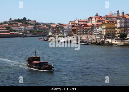 A boat cruises on the River Douro, past the Ribeira District, UNESCO World Heritage Site, Porto, Douro, Portugal, - Stock Photo