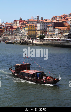 A traditional Rabelo boat, once used for shipping wine grapes, cruises on the River Douro, Porto, Douro, Portugal, - Stock Photo
