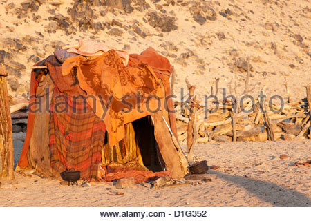 Himba hut covered with patterned blankets, Purros Himba village, northern Namibia, Africa - Stock Photo
