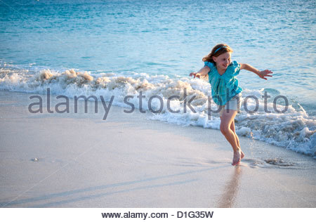 Girl in shorts running from waves on Grace Bay beach, Providenciales, Turks and Caicos Islands,West Indies, Caribbean - Stock Photo