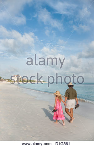 Father and daughter holding hands walking along Caribbean beach, Providenciales, Caicos, Turks and Caicos Islands, - Stock Photo