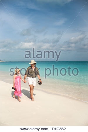 Father and daughter walking along Caribbean beach, Providenciales, Caicos, Turks and Caicos Islands, West Indies, - Stock Photo