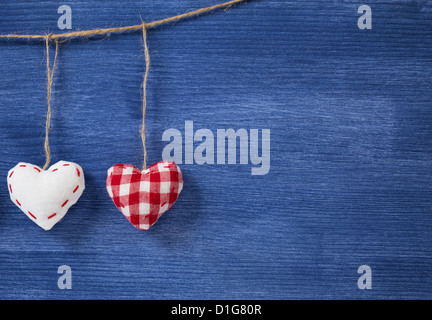 two textile hearts over wooden wall, can be used as a background - Stock Photo