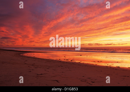 After sunset, the sky lights up. It reflects vibrant colors on the ocean, the cloudy sky and on the sand in Carlsbad, - Stock Photo