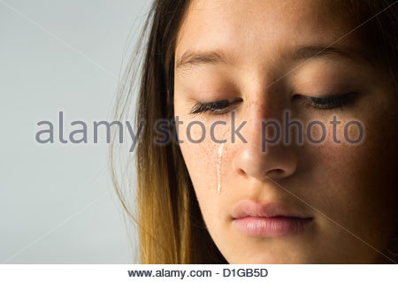 close up of a teen girl with a tear running down her face. - Stock Photo