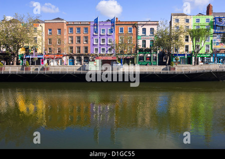 Horizontal view of the colourful buildings along Batchelor's Walk reflected in the River Liffey in Dublin on a sunny - Stock Photo