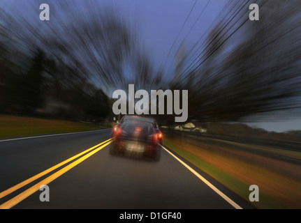 Car Speeding Down Rural Road - Stock Photo