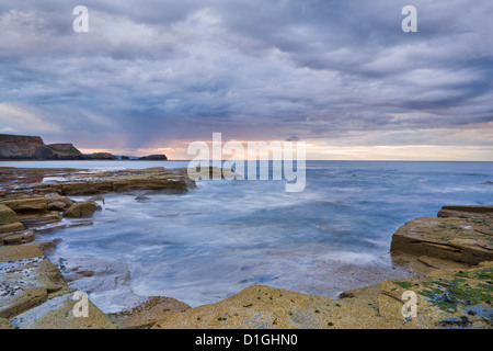 A showery evening at low tide in Saltwick Bay, North Yorkshire, Yorkshire, England, United Kingdom, Europe - Stock Photo