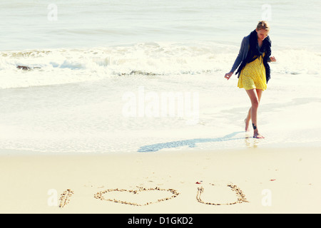 Young woman on a sunny beach with 'I Love you' written in the sand in front of her. - Stock Photo