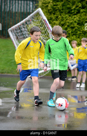 School boys dribbling a football at the end of a rained off practice match at Our Lady & St. Werburgh's Catholic - Stock Photo