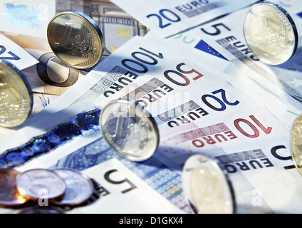 Euro banknotes and coins in various denominations close up. - Stock Photo