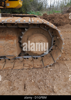 Closeup detail of the caterpillar track of a large tracked excavator on a highway construction site UK - Stock Photo