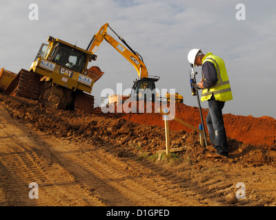 Surveyor setting out engineer checks batter rail peg on UK new road construction site wearing high vis visibility - Stock Photo