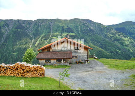 Swiss Cottage in the Alps in the Canton Graubünden, Switzerland - Stock Photo