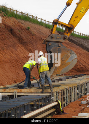 Pouring concrete from a digger bucket for a reinforced concrete bridge foundation strip footing vibrating poker - Stock Photo