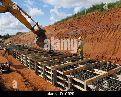 Pouring concrete for a reinforced concrete bridge foundation strip footing uk - Stock Photo