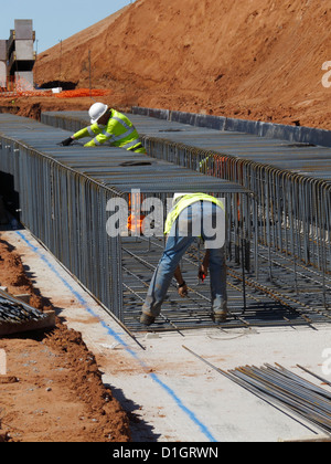 Steel fixer tying reinforcement bars in a bridge foundation base construction building site civil engineering UK - Stock Photo