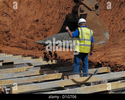 Pouring concrete from a digger bucket for a reinforced concrete bridge foundation strip footing UK - Stock Photo