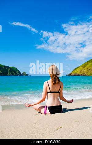 Woman meditating at Mawun Beach, South Lombok, Indonesia, Southeast Asia, Asia - Stock Photo