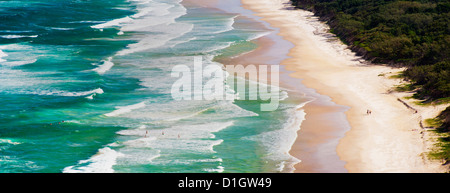 Panoramic photo of surfers heading out to surf on Tallow Beach at Cape Byron Bay, New South Wales, Australia, Pacific - Stock Photo