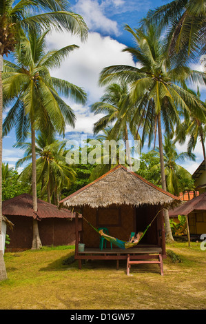 Tourist relaxing in a hammock on a bamboo beach hut on the Thai island of Koh Lanta, South Thailand, Southeast Asia, - Stock Photo