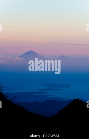 Sunset over Mount Agung and Mount Batur on Bali, and the Three Gili Isles taken from Mount Rinjani, Lombok, Indonesia - Stock Photo