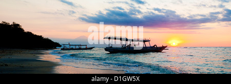 Mount Agung on Bali and fishing boats silhouetted against a sunset, Gili Trawangan, Gili Isles, Indonesia, Southeast - Stock Photo